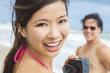 Asian Woman Couple at Beach Taking Video or Photograph