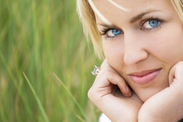 Woman With Blond Hair Blue Eyes Green Background