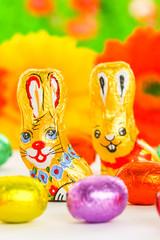 Ostern: Schokoladenhase mit Ostereiern vor Blumen