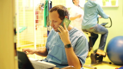 doctor talking on cellphone and checking results on laptop