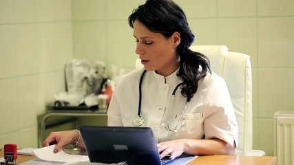 Young female doctor working with laptop in the hospital