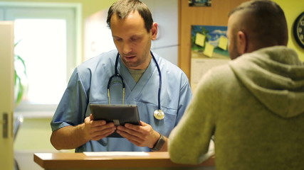 Young doctor talking with patient at hospital reception desk
