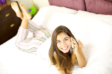 Happy girl on the phone in bed smiling and looking