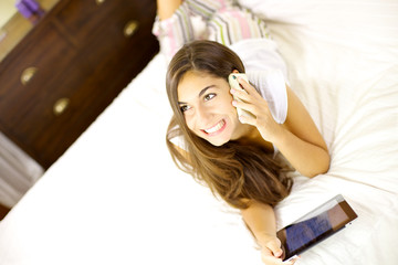 Happy woman on the phone lying in bed with tablet