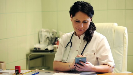 Young female doctor sitting with smartphone in the hospital