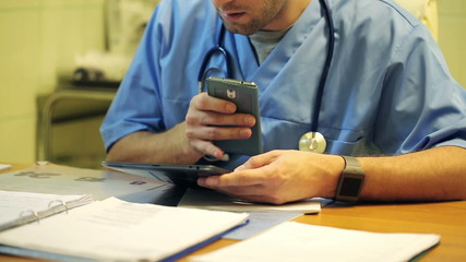 Young male doctor sitting with smartphone in the hospital