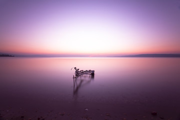 long exposure of sunset from seaside with a boat carrier at sea