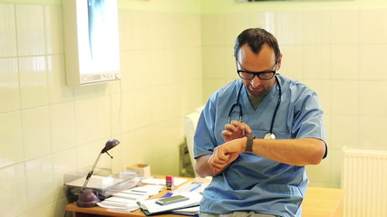 Young male doctor sitting with smartwatch in the hospital
