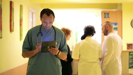 Young doctor with tablet computer in hospital hall