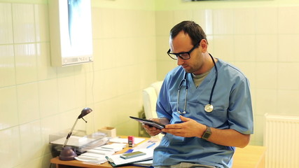 Young doctor with tablet computer sitting on in hospital
