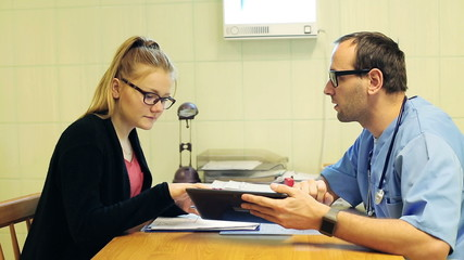 Doctor using tablet and talking about examination results