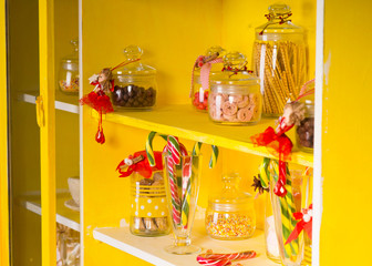 Candies on Glass Jars at Yellow Shelves