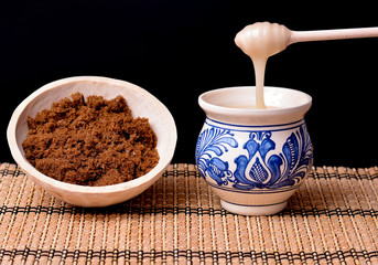 Brown sugar and honey in wooden bowl and clay painted cup
