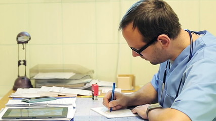 Male doctor hands writing rx prescription in hospital