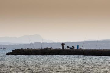Beach fishing from the breakwater in Santa Pola, Alicante,