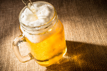 Pouring beer into a mason jar.