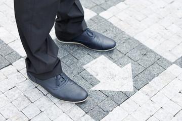 Pfeil vor Schuhen zeigt in eine Richtung