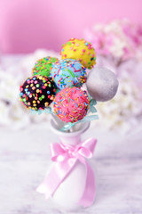 Sweet cake pops in vase on table on pink background