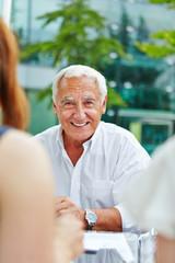 Lächelnder alter Manager sitzt am Tisch