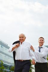 Alter und junger Geschäftsmann laufen zum Termin