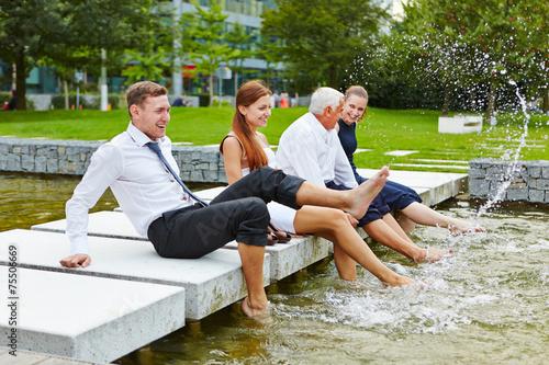 Leinwanddruck Bild Geschäftsleute spritzen Wasser im Sommer