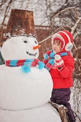 child girl in red jacket making snowman in winter garden