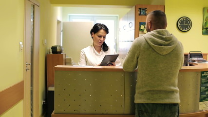 Patient and nurse with tablet conversing at hospital reception