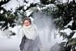 beautiful girl in winter throws snow