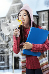 Asian student in winter clothes shouting with megaphone