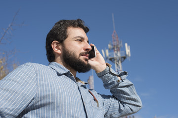 hipster talking on phone next to an antenna of telecommunication