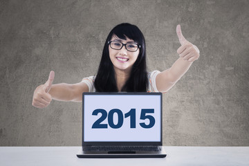Cheerful girl with laptop showing thumbs-up