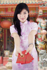 Chinese girl showing envelope in shrine