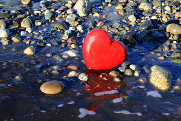 Red heart on the beach.