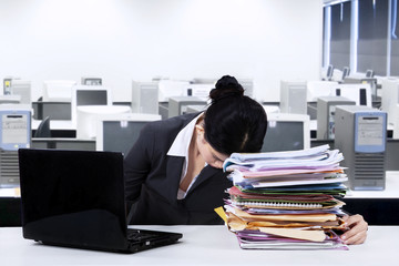 Exhausted worker napping over documents