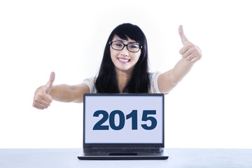 Girl with thumbs-up and numbers 2015 on laptop