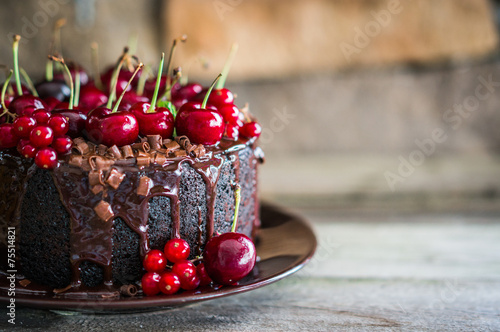Fototapeta Chocolate cake with cherries on wooden background