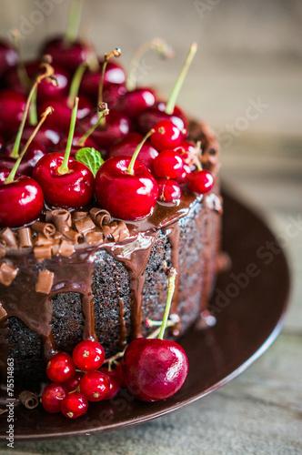 Fototapeta Chocolate cake with cherries on wooden background