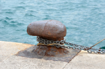 Old mooring bollard and chain in port, Croatia
