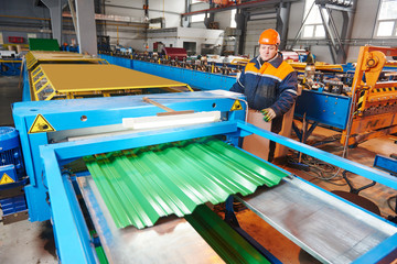 worker at metal sheet profiling factory