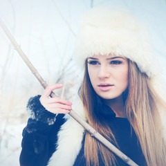 Beautiful young blonde woman with fur hat in winter