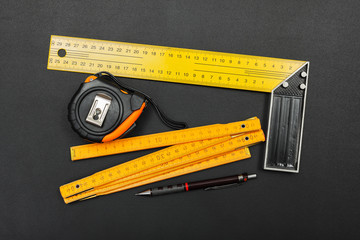 Measuring tools and pencil on black