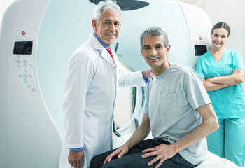 Man in 40s ready to undergo MRI scan, assisted by two smiling do
