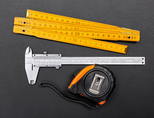 Measuring tools on black: ruler, caliper and tape