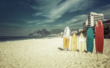 Surfboards standing upright in bright sun on the beach at Ipanem