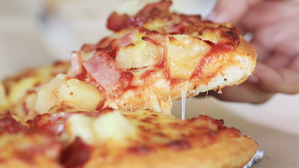 Close up a hand taking a slice pizza.