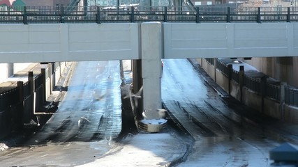 Cars pass under a bridge followed by pigeons