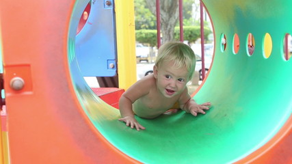 baby girl plays on the playground and climbs into the pipe