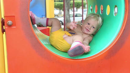 baby girl on the playground plays in the pipe