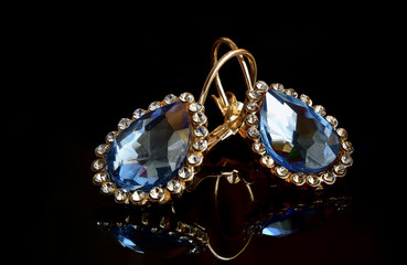 Earrings from gold against a dark background.