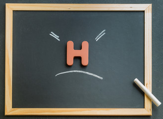 Wooden H character on black board